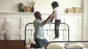 Pai africano feliz que joga com o filho da criança que salta na cama filme