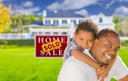 Pai afro-americano e filho na frente do sinal e da casa vendidos Imagem de Stock Royalty Free