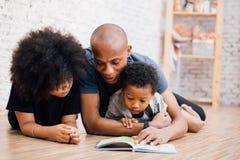 Pai afro-americano que lê uma história da fábula do conto de fadas para crianças em casa fotografia de stock royalty free