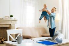 Pai alegre atento que joga com um bebê ao ser em casa Imagens de Stock Royalty Free