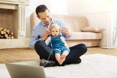 Pai alegre atento que põe os fones de ouvido sobre seus bebê e sorriso fotos de stock
