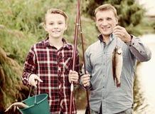 Pai amigável com o filho que olha peixes no gancho fotografia de stock