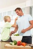 Pai & filho que preparam a salada na cozinha moderna Fotos de Stock