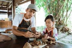 Pai asiático e filha que trabalham com argila fotografia de stock royalty free