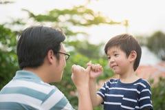 Pai asiático e seu filho que fazem uma promessa do dedo mínimo fotos de stock royalty free