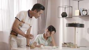 Pai asiático que anda na sala de leitura que fala ao filho frustrado com trabalhos de casa vídeos de arquivo