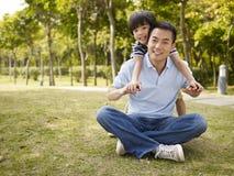 Pai asiático e filho que têm o divertimento no parque Foto de Stock