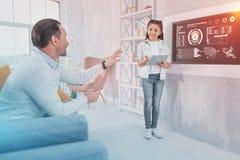 Pai atento que fala a sua filha inteligente ao verificar seus trabalhos de casa imagem de stock