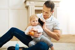 Pai atento que organiza uma conversa do telefone para uma criança e que olha calmo Imagem de Stock