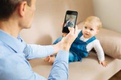 Pai atento que toma uma foto de seu bebê bonito no sofá Imagens de Stock Royalty Free