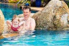Pai ativo que ensina sua filha da criança nadar na associação no recurso tropical Fotos de Stock Royalty Free