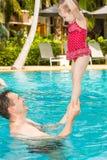 Pai ativo que ensina sua filha da criança nadar na associação no recurso tropical Imagens de Stock