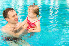 Pai ativo que ensina sua filha da criança nadar na associação no recurso tropical Imagem de Stock