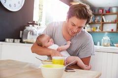 Pai With Baby Daughter que verifica o telefone celular na cozinha Imagem de Stock