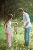 Pai bonito novo, mãe e filho pequeno da criança contra árvores verdes fotos de stock