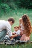 Pai bonito novo, mãe e filho pequeno da criança contra árvores verdes imagem de stock royalty free