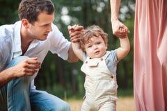 Pai bonito novo, mãe e filho pequeno da criança contra árvores verdes foto de stock royalty free