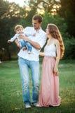 Pai bonito novo, mãe e filho pequeno da criança contra árvores verdes imagens de stock royalty free