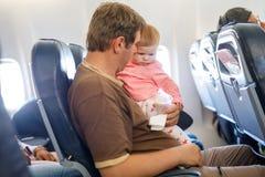 Pai cansado novo e sua filha de grito do bebê durante o voo no avião que vai em férias Paizinho que guarda e que joga fotos de stock royalty free