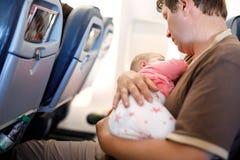 Pai cansado novo e sua filha do bebê que dormem durante o voo no avião que vai em férias Paizinho que guarda o bebê sobre imagem de stock royalty free