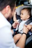 Pai caucasiano que põe o bebê de sorriso no banco de carro da criança foto de stock royalty free