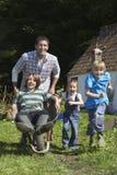Pai And Children Racing com o carrinho de mão fora da casa de campo Imagens de Stock