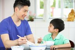 Pai chinês e filho que sentam em casa comer Fotografia de Stock