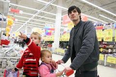 Pai com as crianças na loja Imagens de Stock