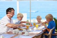 Pai com as crianças que comem o café da manhã no restaurante do recurso Imagens de Stock Royalty Free