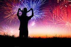 Pai com a criança que olha o fogo de artifício Fotos de Stock Royalty Free