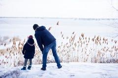 Pai com daugther que olha o rio congelado com neve ao redor fotografia de stock