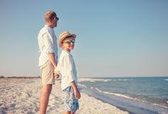 Pai com estada pequena do filho na praia do mar fotos de stock