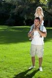 Pai com a filha em ombros em um parque Imagens de Stock