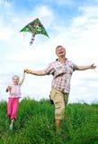 Pai com a filha que joga com papagaio fotografia de stock royalty free