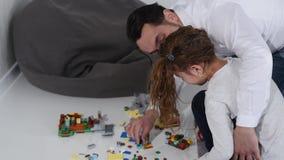 Pai com a filha que joga com um construtor video estoque