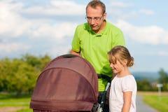 Pai com o buggy da criança e de bebê foto de stock royalty free