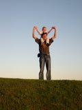 Pai com o filho em ombros no pôr-do-sol Fotografia de Stock Royalty Free