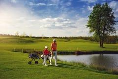 Pai com o filho no campo do golfe Imagens de Stock
