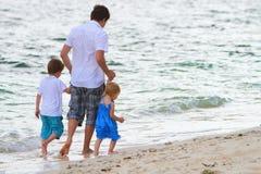 Pai com os dois miúdos que andam ao longo da praia imagem de stock royalty free