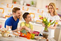 Pai com os ovos colorindo do filho quando a mãe arranjar tulipas no vaso foto de stock