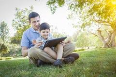 Pai considerável e filho da raça misturada que jogam na tabuleta do computador Foto de Stock Royalty Free