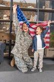 pai considerável no uniforme e no filho do exército com a bandeira grande dos EUA fotografia de stock