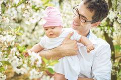 Pai considerável que dá uma volta em um pomar com um bebê Imagens de Stock