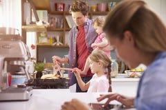 Pai Cooks Family Meal enquanto a mãe usa a tabuleta de Digitas fotos de stock