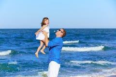 Pai da família que guarda a filha que joga a praia Fotografia de Stock