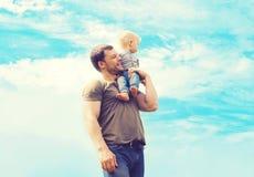 Pai da foto atmosférica do estilo de vida e criança felizes do filho fora sobre o céu azul imagem de stock royalty free