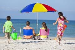 Pai da matriz & família das crianças na praia Fotografia de Stock