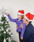 Pai And Daughter Looking na árvore de Natal Fotos de Stock