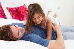 Pai And Daughter Lying na cama junto Fotos de Stock