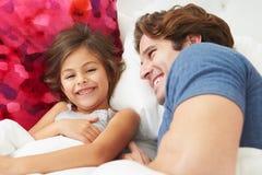 Pai And Daughter Lying na cama junto Imagem de Stock Royalty Free